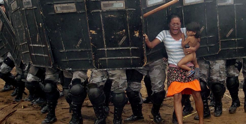 Kobieta trzymająca dziecko próbuje oprzeć się brazylijskiemu oddziałowi policji, powołanemu aby wyeksmitować mieszkańców Manaus. (2008)