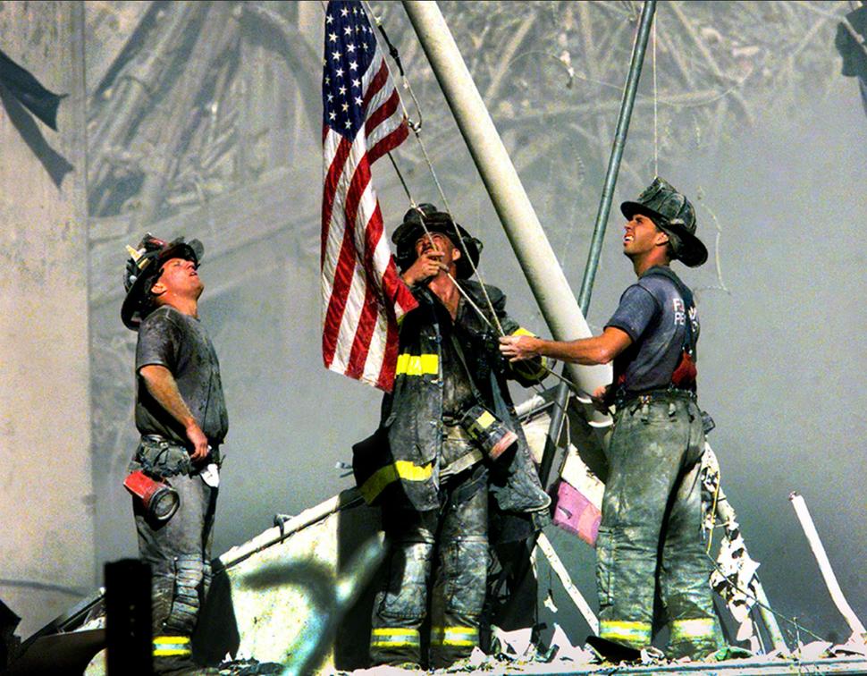 Strażacy stawiają amerykańską flagę na ruinach World Trade Center. (2001)