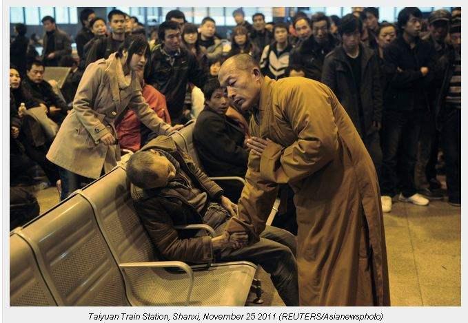 Mnich modli się za zmarłego na stacji kolejowej Shanxi Taiyuan, Chiny. Mężczyzna zmarł z przyczyn naturalnych czekając na pociąg; 25.11.2011.