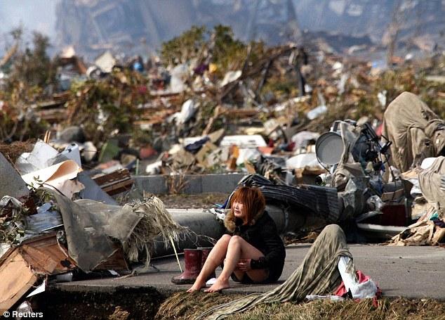 Zdruzgotana dziewczyna na zgliszczach po przejściu tsunami w Japoni, 2011.