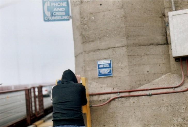 Mężczyzna używający telefonu zaufania dla samobójców na moście Golden Gate.