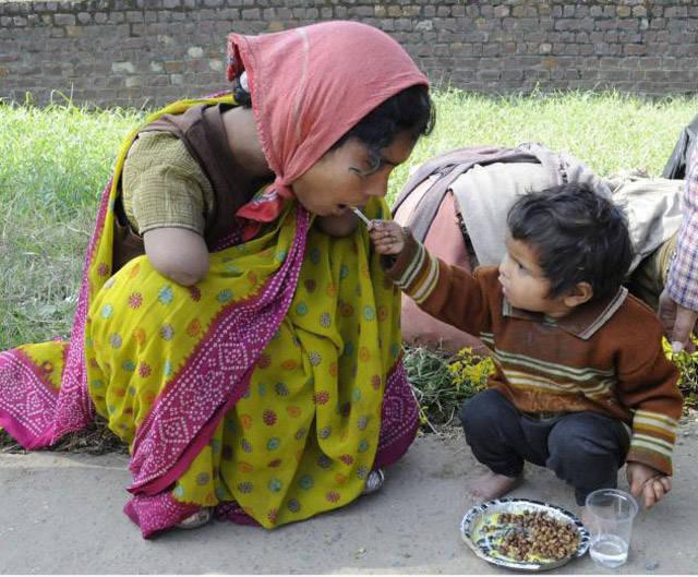 2-letnie dziecko karmiące swoją pozbawioną rąk mamę