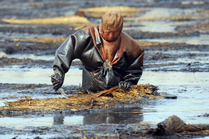 Robotnik próbuje oczyścić wodę z ropy. Dalian, Liaoning.