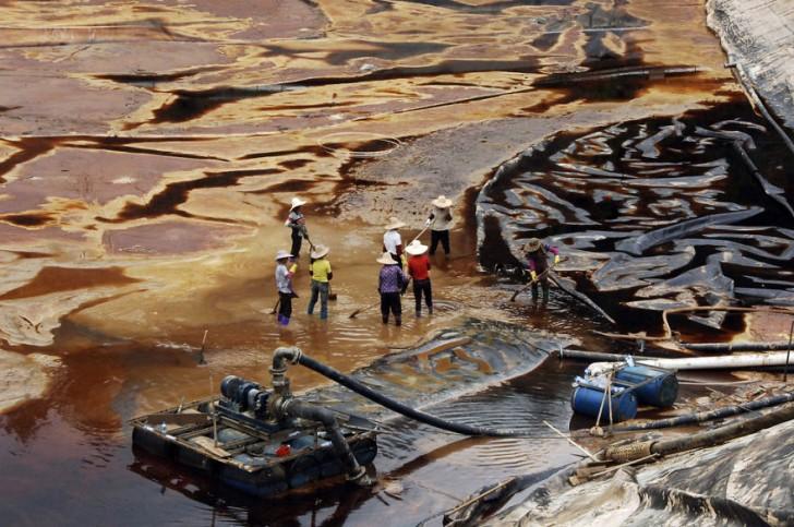 Robotnicy próbują zatamować wyciek ropy. Shanghang, Fujian.