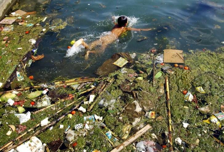 Dziecko pływa w zanieczyszczonym zbiorniku wodnym.