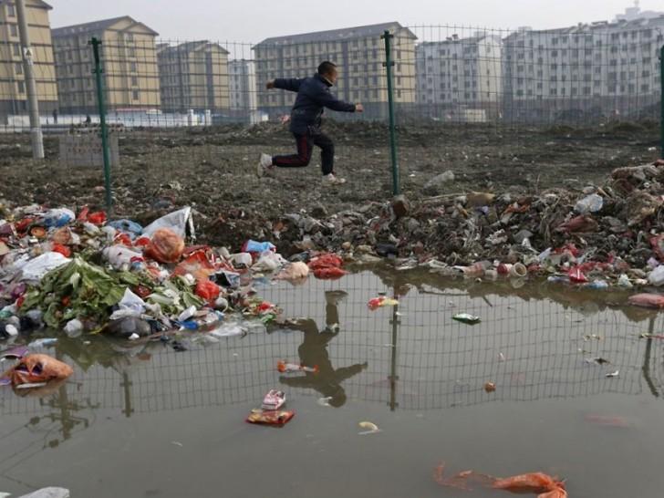 Chłopiec skaczący przez śmieci. Jiaxing.