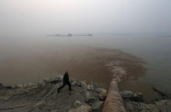 Mężczyzna spacerujący obok rury wylewającej zanieczyszczenia do rzeki Jangcy.