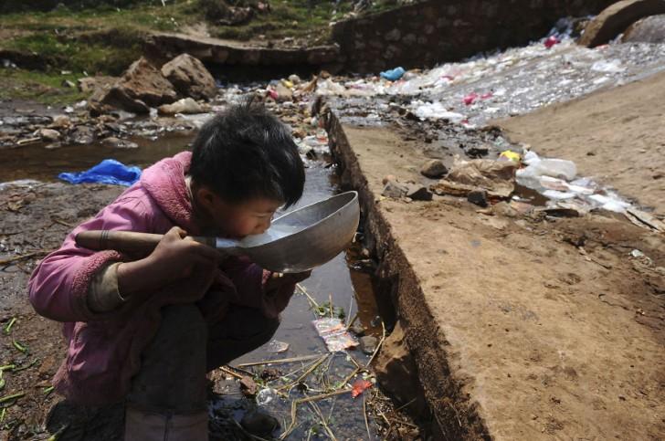 Dziecko pijące wodę ze strumienia. Fuyuan, prowincja Yunnan.