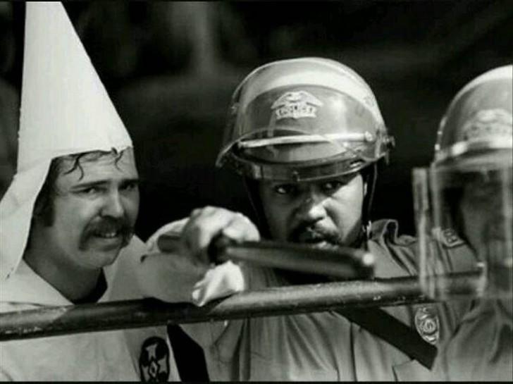 Czarnoskóry policjant chroni członka Ku Klux Klanu podczas manifestacji.