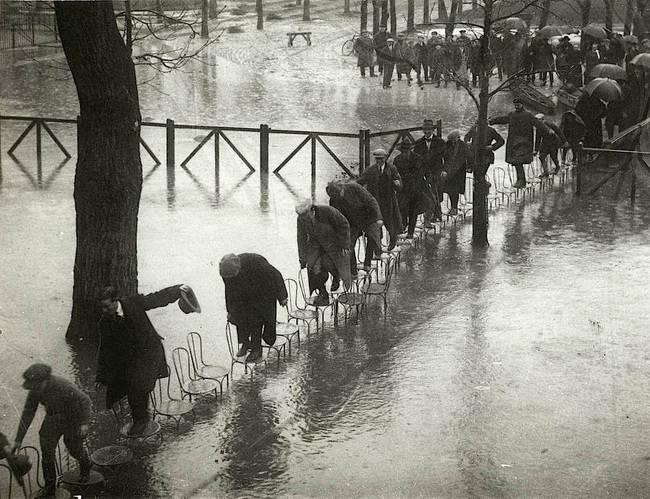 Grupa ludzi próbuje przejść przez wodę podczas wielkiej powodzi, Paryż 1924.