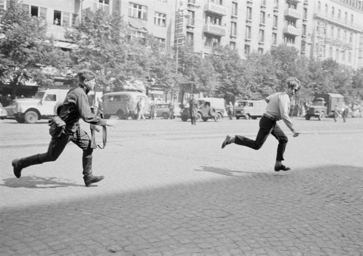 Radziecki żołnierz goni mężczyznę, który rzucił kamieniem w czołg, Czechy, 1968.