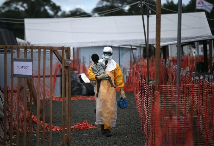 a-doctors-without-borders-health-worker-in-protective-clothing-carries-a-child-suspected-of-having-ebola-in-the-groups-treatment-center-on-oct-5-in-liberia