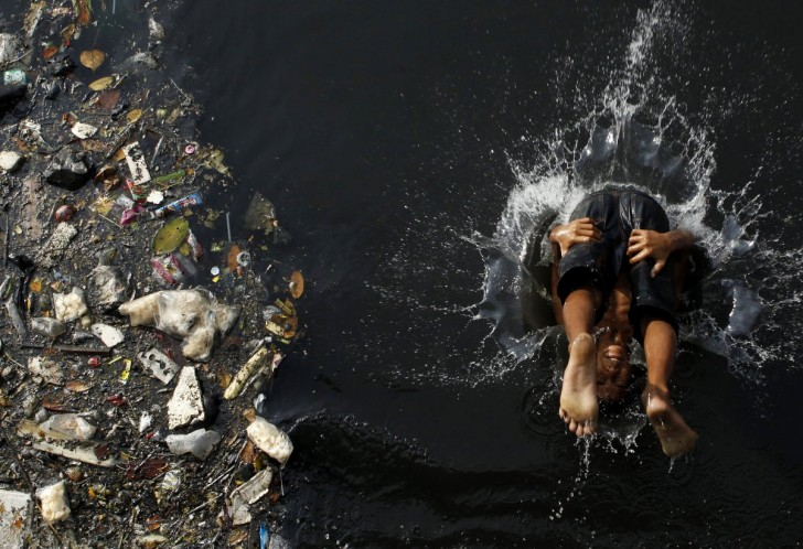 as-our-world-grows-its-becoming-disturbingly-polluted-this-boy-cannonballs-into-a-polluted-river-in-jakarta-indonesia-while-piles-of-garbage-drift-by-next-to-him