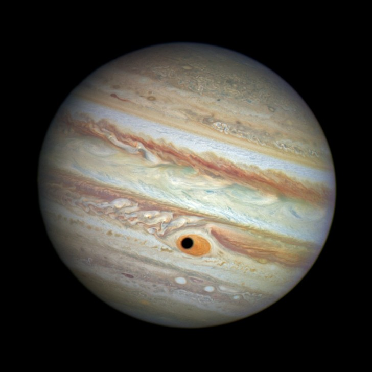 on-april-21-the-hubble-telescope-captured-what-looks-like-a-black-hole-in-jupiters-great-red-spot--but-really-its-the-shadow-of-the-jovian-moon-ganymede