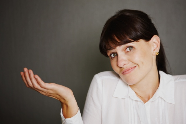 Portrait of woman shrugging and looking at the camera with copyspace