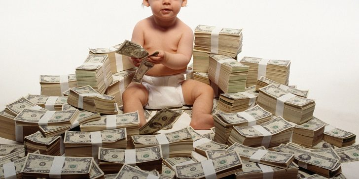 Toddler sitting on stacks of money