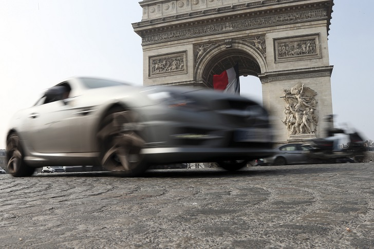 Cars and scooters drive around the Arc de Triomphe, seen in background, in the center Paris, France, Wednesday, March 18, 2015. Paris police have lowered the speed limit and ordered a halt to burning of trash as part of emergency measures triggered by a spike in air pollution, months before the city hosts a major international climate conference. (AP Photo/Francois Mori)