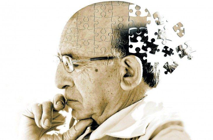 Artystyczna wizja przedstawiająca chorobę Alzheimera. Obrazek przedstawia mężczyznę w podeszłym wieku w zamyślonej pozie. Tylna część jego głowy odlatuje w formie pojedynczych puzzli poza krawędź obrazka. Przedstawia to spadek sprawności umysłowej oraz zanik pamięci.