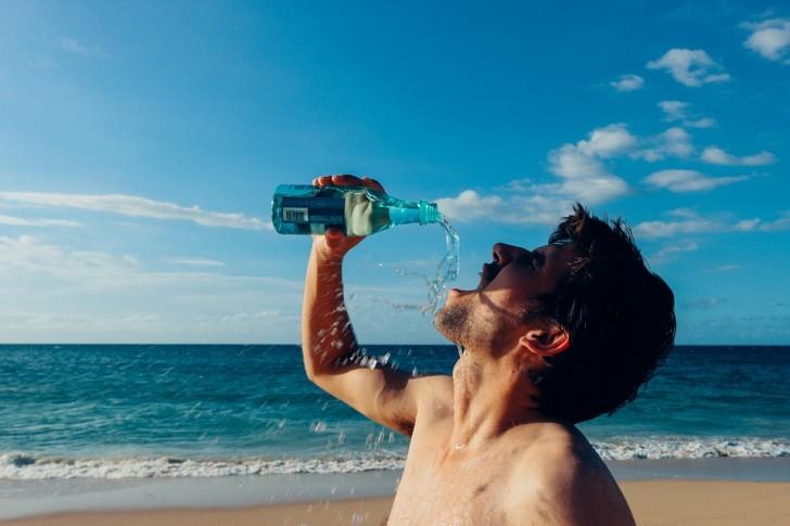 Zdjęcie mężczyzny zachłannie pijącego wodę na plaży.