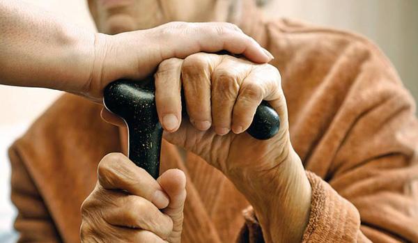 Na zdjęciu widoczny starszy człowiek podpierający się o laskę.