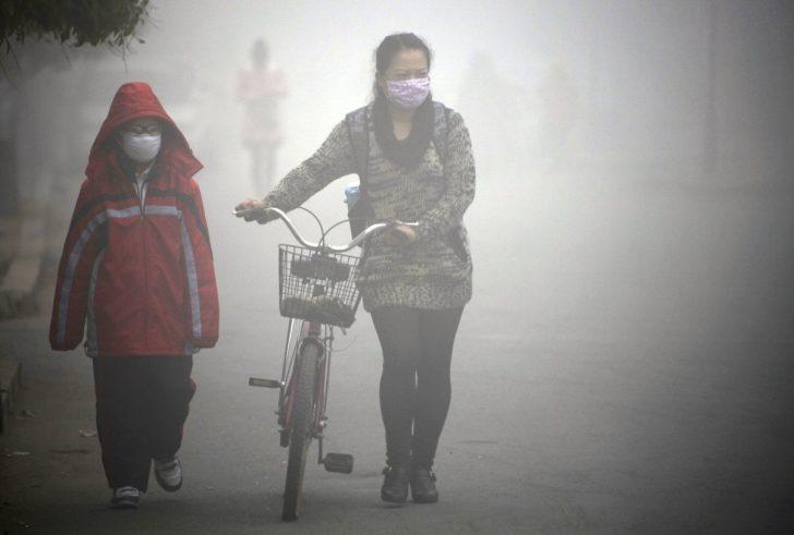 Zdjęcie przedstawia Chińczyków poruszających się w gęstym smogu.