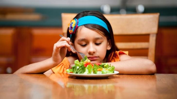 Na zdjęciu dziewczynka niechętnie spożywająca swój posiłek.