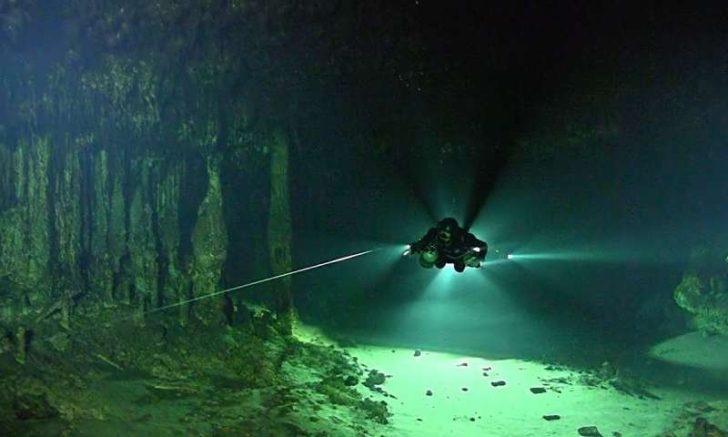 Zdjęcie przedstawia nurka płynącego w ciemności przez podwodną jaskinię.